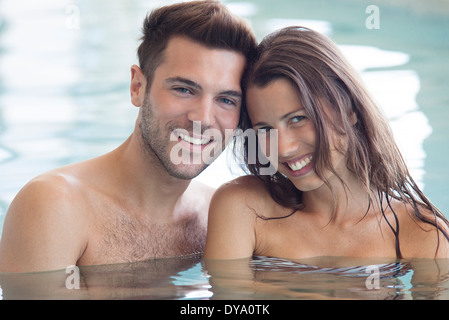 Couple relaxing together in pool, portrait - Stock Photo