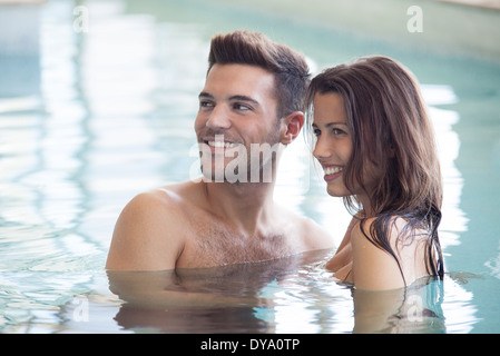 Couple relaxing together in pool - Stock Photo