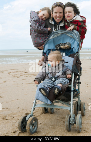 Mother with three children at the beach - Stock Photo