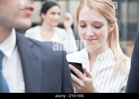 Businesswoman checking smartphone while on the move - Stock Photo