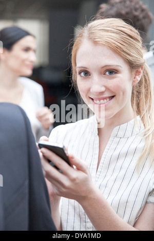 Businesswoman checking smartphone on the move - Stock Photo