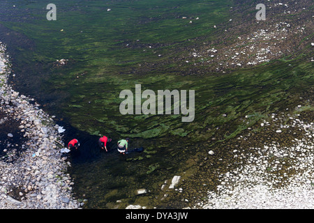 Women dressed in traditional clothes working with dyed fabrics on the bank of the Duliu River in Congjiang, Guizhou, - Stock Photo