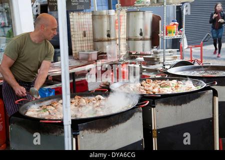 Man Cooking Chicken Dish in Large Pan at Portobello Market in London W11 - UK - Stock Photo