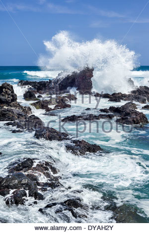 High surf breaking onto rocks at Hoopika Bay on the island of Maui in the state of Hawaii USA - Stock Photo