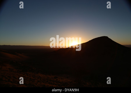 Sunrise over baron desert landscape in Morocco beyond the Atlas mountain ranges, with rays of sunlight overlapping - Stock Photo