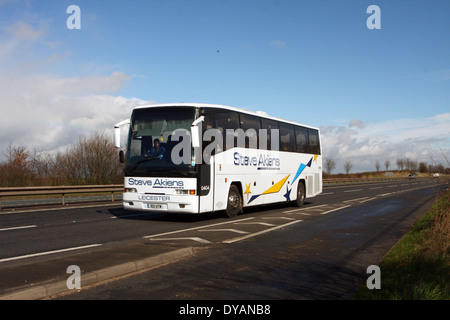 A Steve Akiens coach traveling along the A46 dual carriageway in Leicestershire, England - Stock Photo