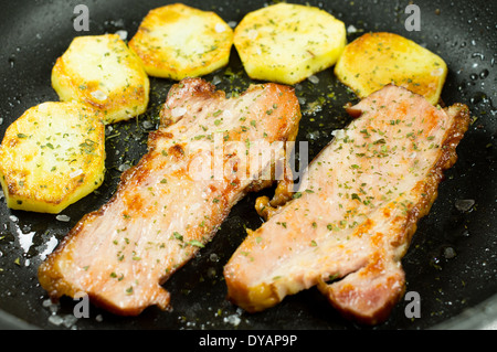 Bacon and potatoes fried in a pan. - Stock Photo