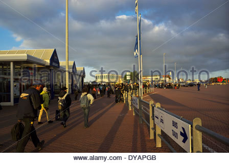 People disembarking and gathering in the ferry plaza on the East Frisian island of Norderney, Germany. - Stock Photo
