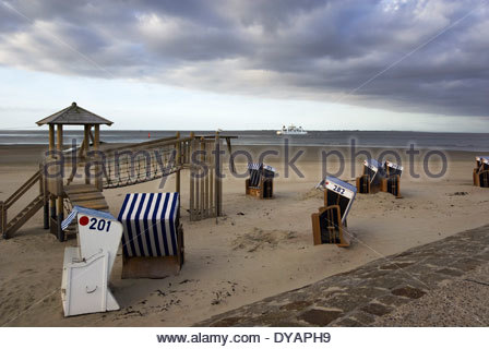 Beach chairs and recreation await the day's vacationing families, as ferries come and go in the distance, Norderney, - Stock Photo