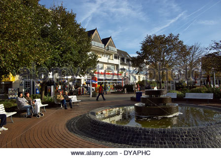 People enjoy morning sun by the fountain at the Kurplatz, Norderney, Germany. - Stock Photo