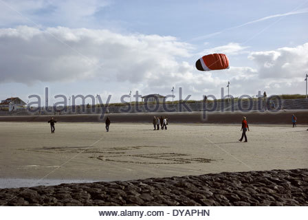 A couple launches an airfoil sport kite on the beach of Norderney, Germany. - Stock Photo
