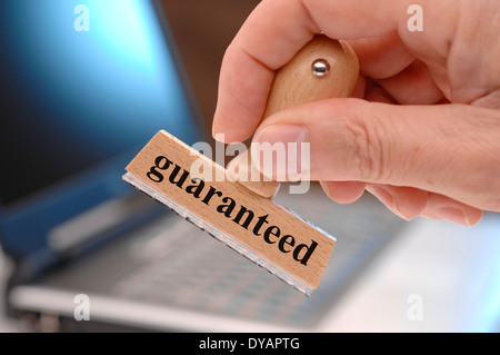 guaranteed marked on rubber stamp in hand - Stock Photo