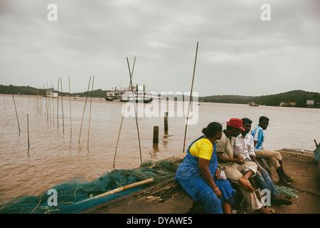 Locals enjoying near the ferry bank in Goa. - Stock Photo