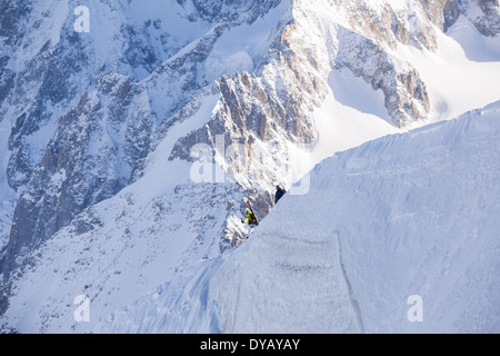 Skiers descend a path from the Aiguille Du Midi (3842m) mountain top above Chamonix Mont-Blanc, to ski the Vallee - Stock Photo