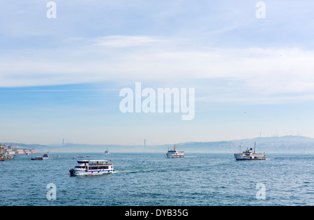 View of local ferries and tour boats on the Golden Horn looking towards the Bosphorus Bridge, Istanbul, Turkey - Stock Photo