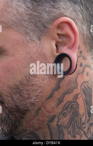 side view of a man with a stretched ear lobe and Tattoos - Stock Photo