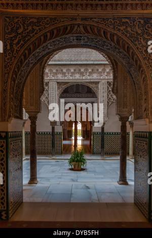 Through an archway into the Patio de las Muñecas in the Palacio del Rey Don Pedro, El Real Alcázar, Sevilla, Spain - Stock Photo