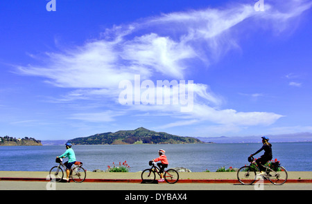 family of cyclists ride on Bridgeway in Sausalito California - Stock Photo