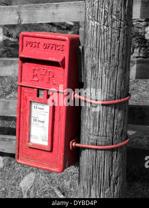 Rural bright red Post Office postal Box fixed to wooden post in English countryside - Stock Photo