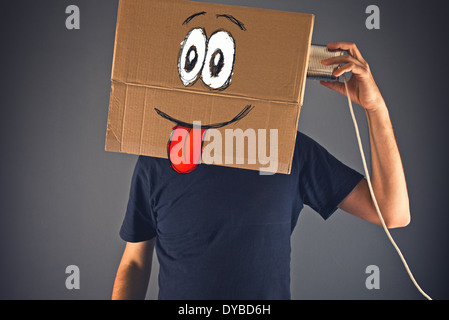 Man with cardboard box on his head using tin can telephone for conversation. Happy face expression. - Stock Photo