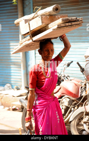 Delhi, India. April 6th 2014. An elderly lady carries a heavy load in a typical backstreet of Old Delhi, India. - Stock Photo