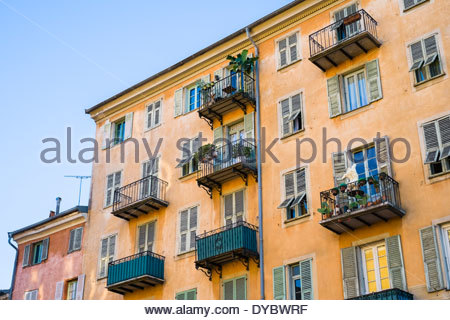Old colorful buildings with shutters on windows on Place Saint François, Vieille Ville (Old Town), Nice, France - Stock Photo