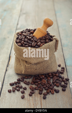Sack of coffee beans with scoop on wooden background closeup - Stock Photo
