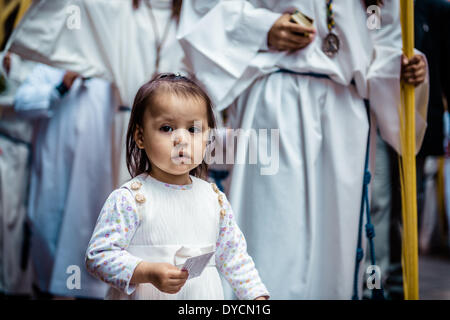 Barcelona, Spain. April 13th, 2014: A very young worshiper with the brotherhoods card during the Palm Sunday procession - Stock Photo