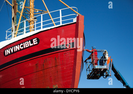 Workman painting ship number. A Converted Fishing boat 'Invincible Dive Vessel' at Fraserburgh, Harbour, UK - Stock Photo