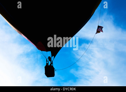 A hot air balloon with two people rising silhouetted in front a hazy blue sky - Stock Photo