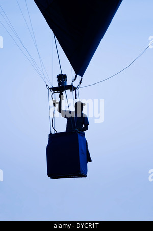A man piloting a one person hot air balloon rising silhouetted in front a hazy blue sky - Stock Photo