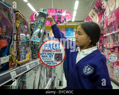 Young Thai / English girl selects a 'Monster High' doll from the shelves in a toy superstore - Stock Photo