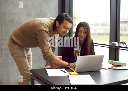 Young woman with her friend at the study desk. Students studying together with laptop. Finding information in library. - Stock Photo