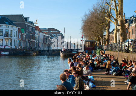 People relaxing in the sun by a river canal in central Utrecht. - Stock Photo
