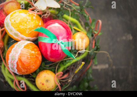 eggs for happy easter handmade colorful in bird nest on old wood - Stock Photo