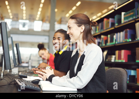 Multiethnic students sitting at table using computers for finding information for their study. Young university - Stock Photo