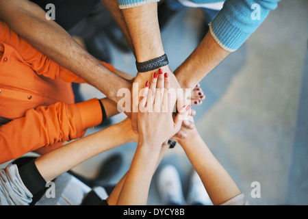 Closeup of stack of hands. Young college students putting their hands on top of each other symbolizing unity and - Stock Photo