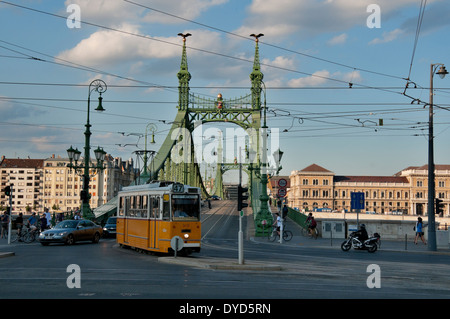 The green Liberty Bridge with a tram cross in Budapest, Hungary at sunset - Stock Photo