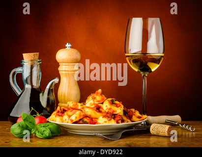 still life with traditional tortellini pasta meal and glass of white wine - Stock Photo
