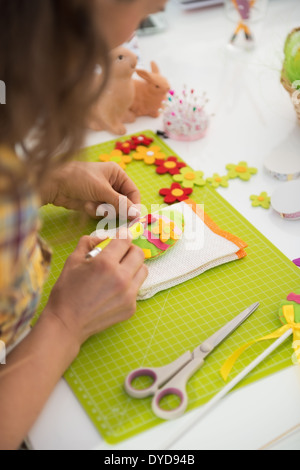 Closeup on young woman making easter decorative egg. rear view - Stock Photo