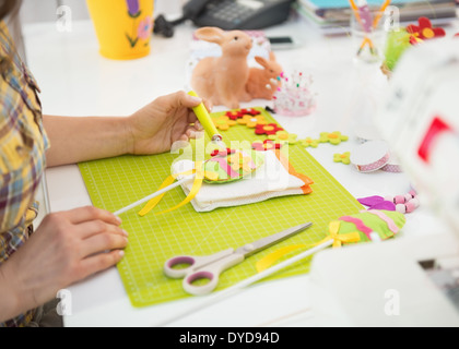 Closeup on young woman making easter decorative egg - Stock Photo