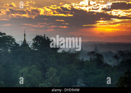 Temples, pagodas and trees in the mist, at sunset, Mrauk U, Sittwe District, Rakhine State, Myanmar - Stock Photo