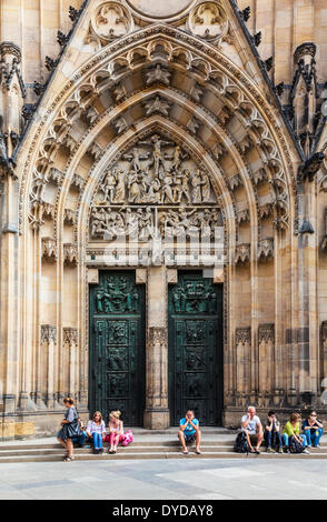 Tourists sitting in front of the medieval gothic front facade of St Vitus Cathedral in Prague. - Stock Photo