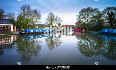 Canal basin on the Grand Union canal showing one of the pubs and a hump backed bridge. - Stock Photo