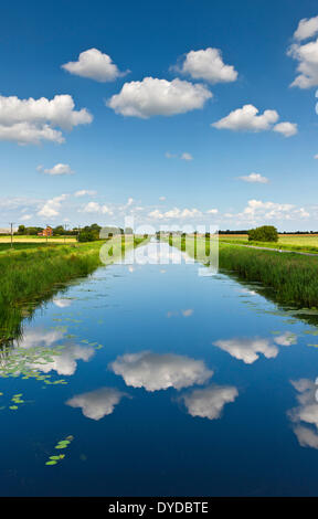 Fluffy white clouds over the sixteen foot drain in Cambridgeshire fenland. - Stock Photo