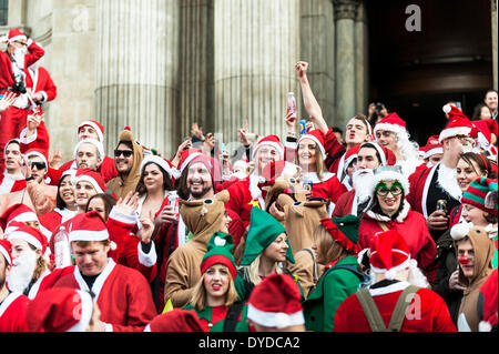 Hundreds of Santas gather on the steps of St Pauls Cathedral to celebrate the annual Santacon. - Stock Photo