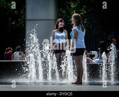 Two girls playing in the fountains on the South Bank in London. - Stock Photo