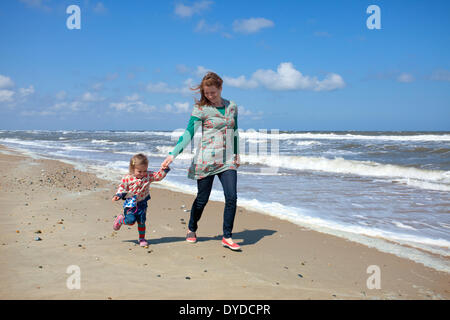 A mother and daughter running along the beach at Horsey on the Norfolk coast. - Stock Photo