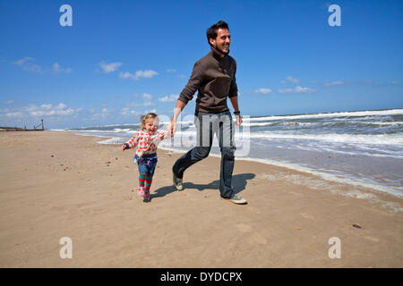 A father and daughter running along the beach at Horsey on the Norfolk coast. - Stock Photo