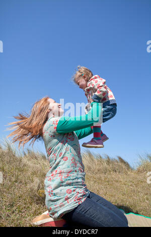 A mother playing with her daughter on Horsey sand dunes on the Norfolk coast. - Stock Photo
